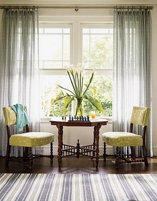 Two comfortable chairs with a table between for a game or a Coffee Klatsch... all in front of a magnificent window and drapes.
