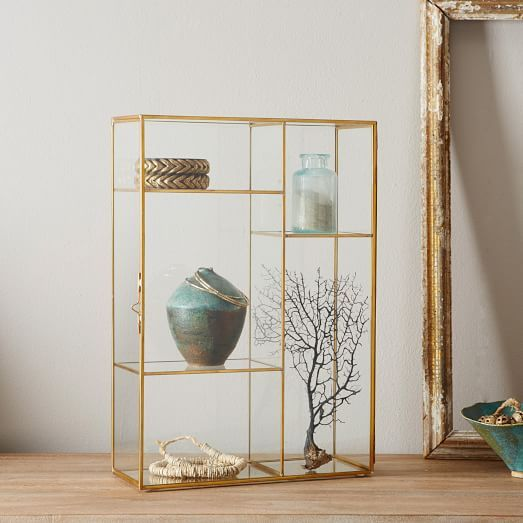 Show off your favorite jewelry, accessories and knickknacks with this glass display case. Its gold-finished frame will make a statement on dressers and vanities alike.