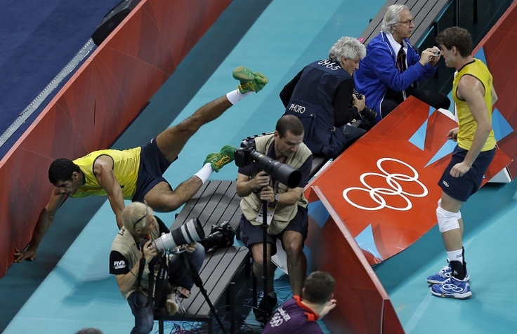 Brazil's Wallace de Souza (4) flies over the photographers bench attempting to save against Argentina during a men's volleyball quarterfinal match at the 2012 Summer Olympics Wednesday, Aug. 8, 2012, in London. (AP Photo/Chris O'Meara)