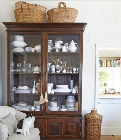 7. Filled with Victoria's collection of ironstone, a Sri Lankan antique cabinet from Susanne Hollis adds a rich anchor to the airy, white room. (Peeshee, her cat, stands guard.)  RELATED: 9 Great Kitchen Storage and Organization Ideas   - CountryLiving.com