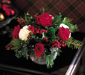 This arrangement is a traditional design. It has used traditional flowers and plants including holly and roses which have the red and green colour scheme.