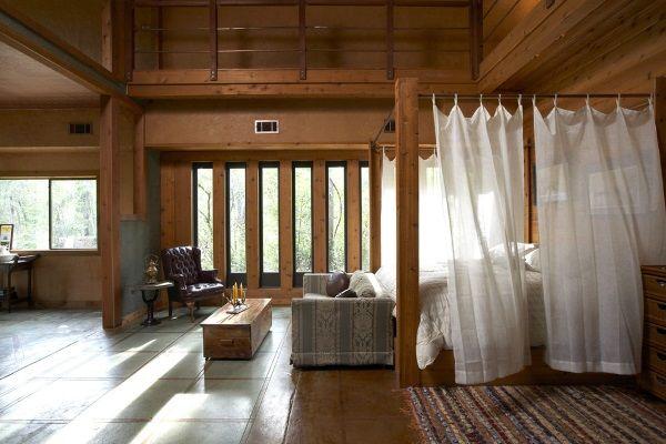 Кровать из деревянных балок с белым балдахином