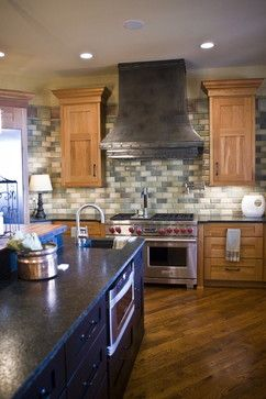 Honey cabinets with black island. Love the Wolf stove and the tile backsplash too!