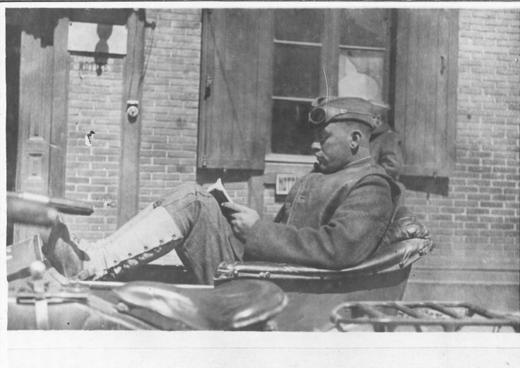 """Creator:Mr. Ranck Description: Black and white photograph of a soldier reading during down time in a car, waiting for orders, Saint Nazaire, France. Notes on back of photo: Reading an ALA book while waiting for orders. Mr. Ranck's Series no. 27. E.B. Thompson, 74111th St. N.W. Subject: World War, 1914-1918, Saint-Nazaire, France. American Library Association. Library War Service. Date: 1919 Format: 7"""" x 9"""" black and white photograph Source: American Library in Paris archives, file 1, no…"""