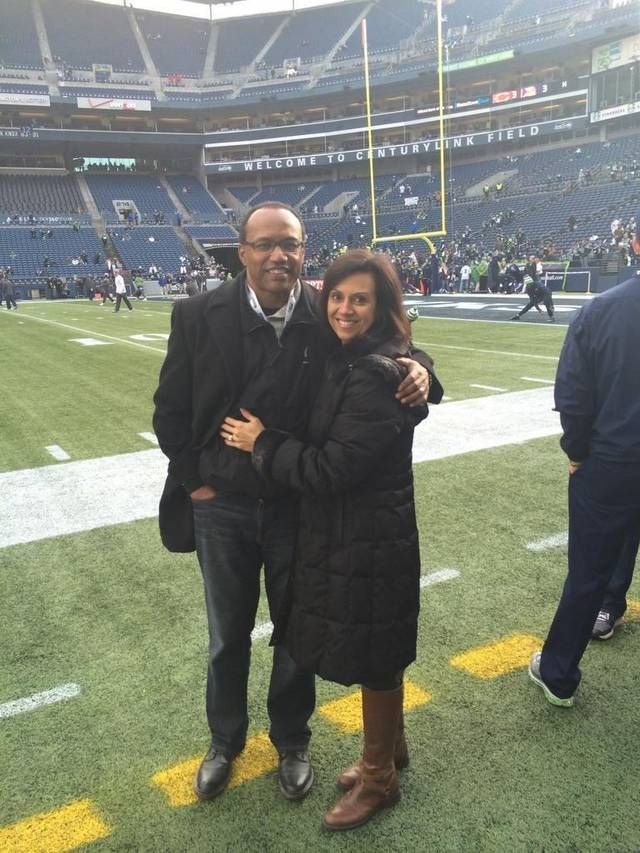 Curt and Ana Warner pose for a photo on the sidelines at CenturyLink Field in Seattle.