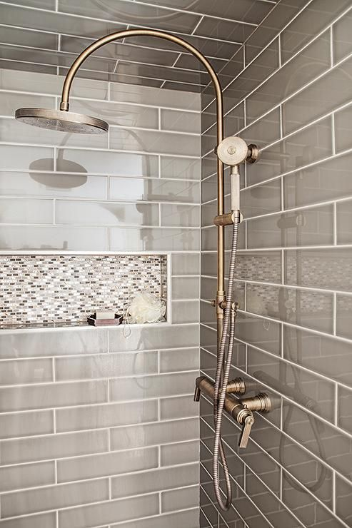 Gray walk in shower boasts ceiling and walls clad in gray tiles fitted with  a white and gray mosaic tiled shower niche as well as a vintage style e