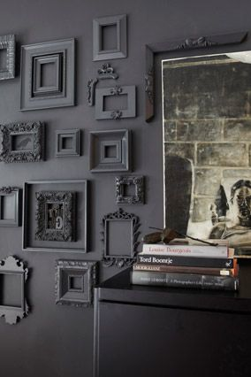 """Hang ghost frames- """"To add faux architectural interest in the living room, cover one blank wall with a collection of cheap frames—find them at discount stores or flea markets. Paint the frames the same shade as the wall color—it's an effect that mimics texture. Choose a high-gloss paint finish on the frames to add shimmer and sophistication and to make them pop from the wall."""""""