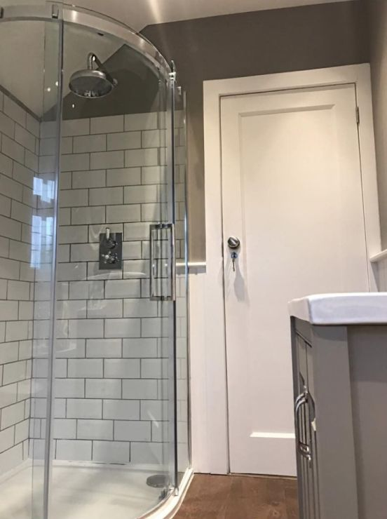 Emily has made a feature of her quadrant shower enclosure by using white metro tiles with dark grouting. The apron shower head and concealed shower valve are in keeping with style of this beautiful grey bathroom.