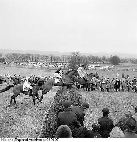 AA069697 Horses and jockeys captured in mid-air at a jump in the Flagg Races point-to-point steeplechase on Flagg Moor, Derbyshire, and being watched by a crowd of spectators. The race is traditionally held on Easter Tuesday each year.   Date1959 Photographer: John Gay