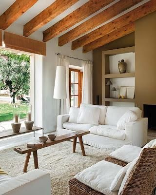 More white couches & white walls, timber accents.  Love the rattan chairs and natural timber coffee table.