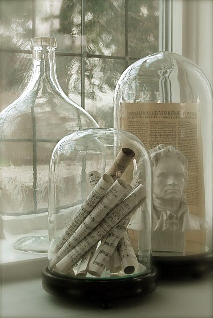 bell jars with ornaments, tickets, statues and mementos that have a theme to put on the dining room table
