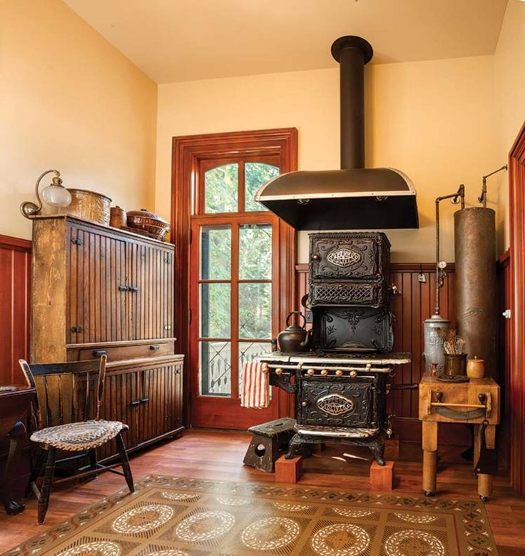 An 1890s Penn Olive cast-iron stove with Art Nouveau styling is accompanied by a side arm and copper water heater. The setback cupboard kitchen at left, an antique found at Rejuvenation, dates from the late 1800s.