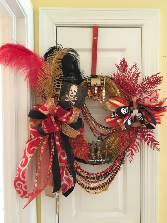 Red, gold and black Gasparilla wreath made on an 18 grapevine. It is adorn with ribbons, beads, feathers, glitter picks, pirate flag, a treasure box, wooden carved pirate, and a pirate ship!  **This wreath is available for pick-up or delivery if you live in South Tampa. If you need it shipped, please convo me for a shipping estimate prior to purchasing.