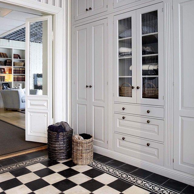 Entre & hall - sliten svart/vitt klinker med mönstrad rand och svart inramning; ljusgrå skåp (samma färg som i köket?)