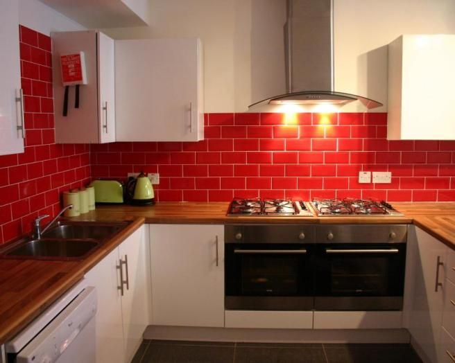 photo of red red tiled splashback kitchen with white kitchen cabinets wooden worktop - Red Kitchen Ideas