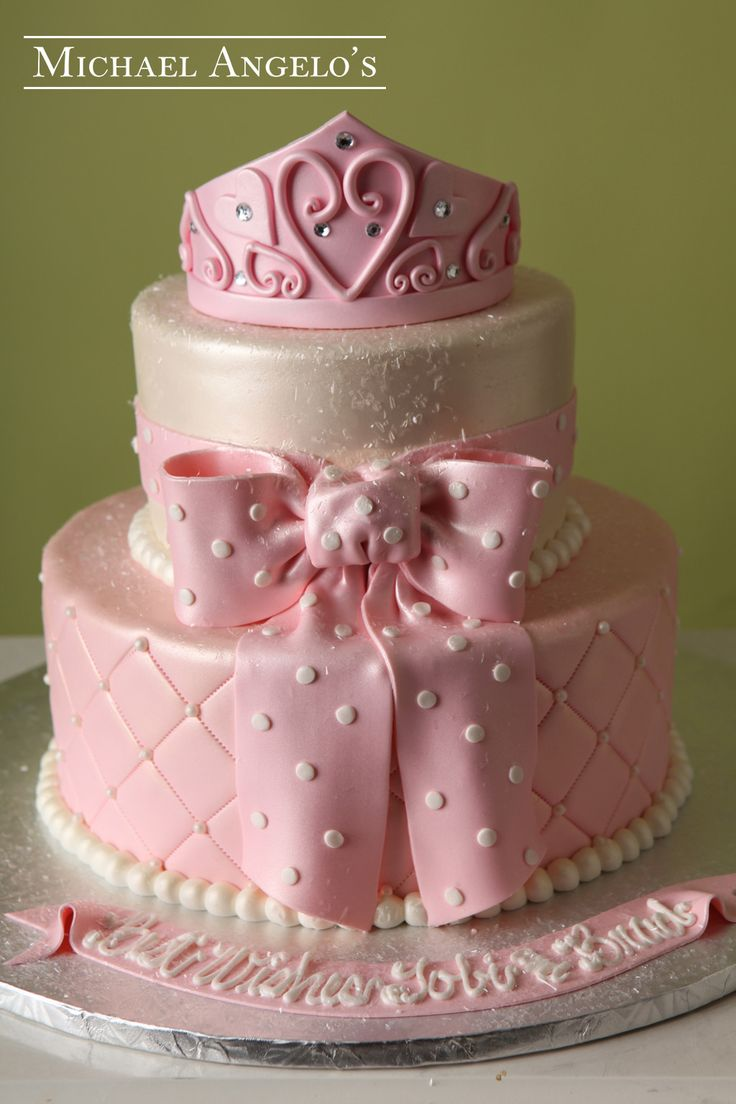 Baby Princess Crown #80Baby This cake is iced in pink fondant and includes a beautiful quiilted pattern with pearls. along with a fondant ribbon & bow. The princess crown tops the cake for a royal appeal.