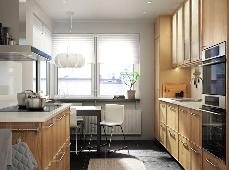 An Oak Kitchen With White Worktops. Combined With Stainless Steel Oven,  Microwave Oven And