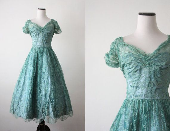 Vintage 1950s dress in a rich adriatic blue satin dress with an intricate lace overlay. Fully flared skirt and a metal zip side.