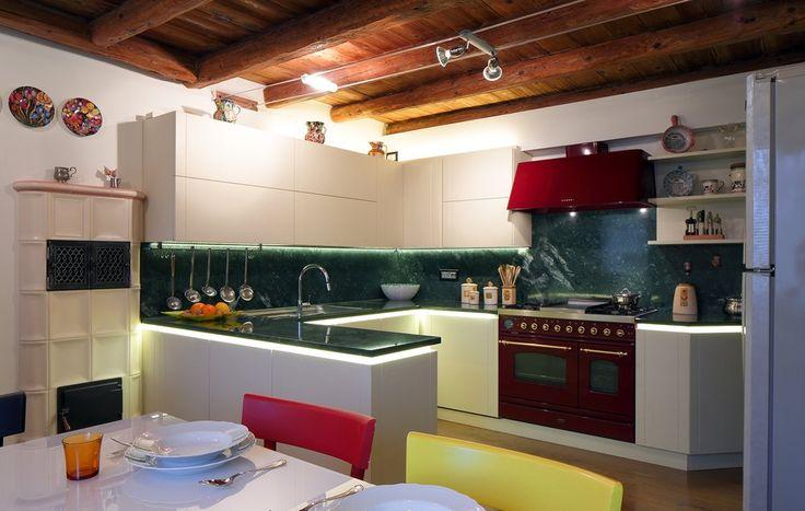 cucina moderna laccata bianca con piano in marmo verde e stufa