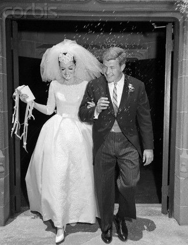 1960s Couple Bride And Groom Arm In Arm Leaving Church Under Shower Of Rice