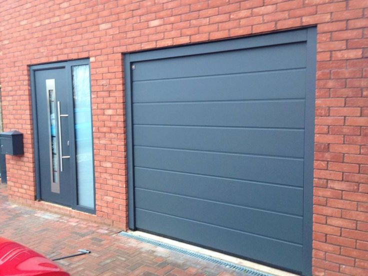 Hormann steel TPS 700 front door with side glass and a Hormann insulated and remote sectional garage door to match both in the colour of Titan Metallic   long bar handle and matching frames