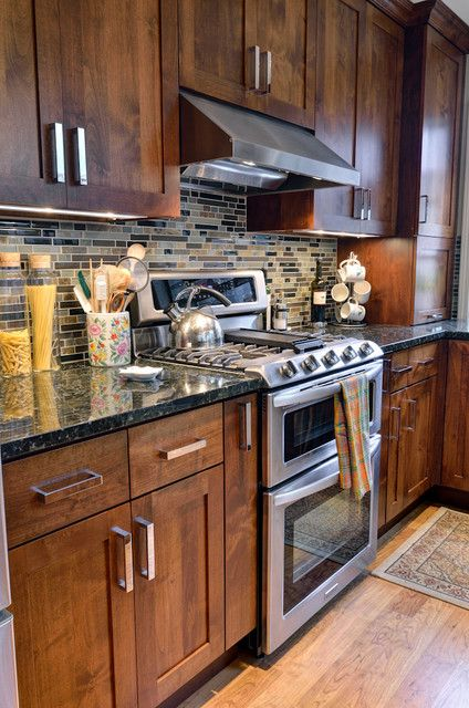 Inspiration for a traditional kitchen in Atlanta along with shaker cupboards, dark wooden cabinets, multicolored backsplash and stainless steel home appliances.