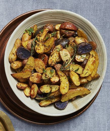 Herb-Roasted Fingerling Potatoes | Roasted potatoes might be one of our favorite ways to round out a meal: half, toss, and stick them in the oven and you've got one of the most satisfying sides known to humans. There are a couple of smart tricks embedded in this recipe: lining your baking sheet with foil means clean up is a cinch (but it's not absolutely necessary so if you're out, don't even worry about it). Then, spraying the foil with a bit on nonstick spray means all the herby garlicky…