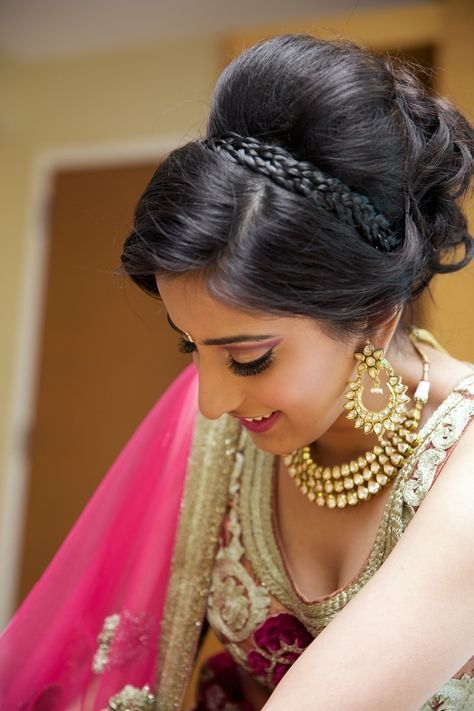 A great way to manage thick hair into a beautiful wedding hair style! Love the way braids are used to hold down and separate a high set bun - a perfect base to pin your dupatta or maang tikka. Love everything about her make up and those stunning jhoomar earrings - Indian bride - Indian bridal make up - Indian bridal hair - Indian bridal jewellery #thecrimsonbride