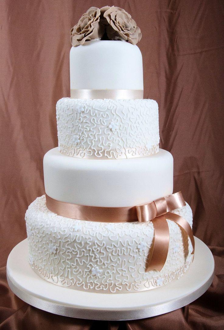 Jednoduchá svadobná torta len z jemnou čipkou a kvetinkami navrchu.