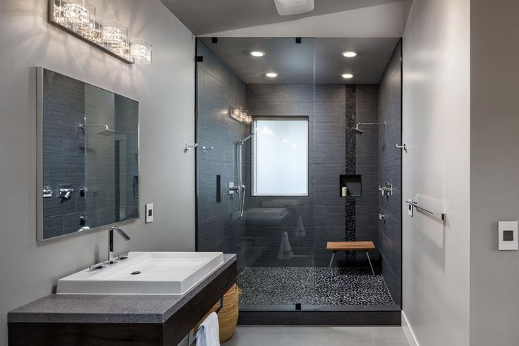 A black-tiled shower provides a subtle contrast in this otherwise neutral, contemporary bathroom. The shape of the modern vanity and sink is echoed throughout the space in the mirror, shower bench, window and even in the luxe light fixture.