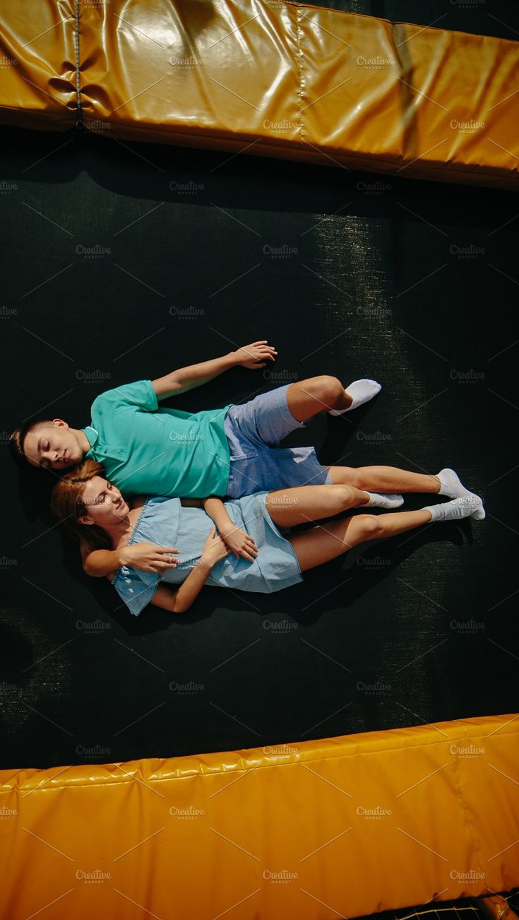 Couple lie on trampoline in the park by Tekso on @creativemarket