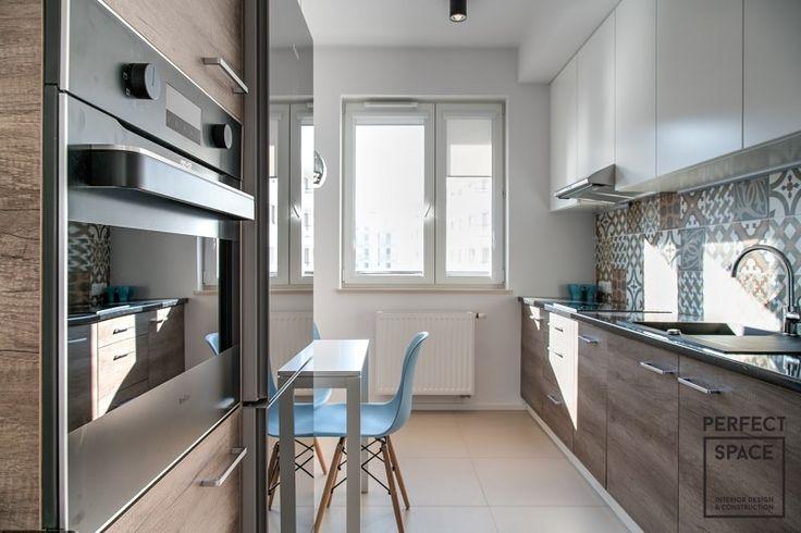 Aranżacja kuchni w klasycznym stylu, fronty szafek w kolorze bieli i brązu, do tego kolorowe płytki nad blatem kuchennym. Jasna i przytulna kuchnia.