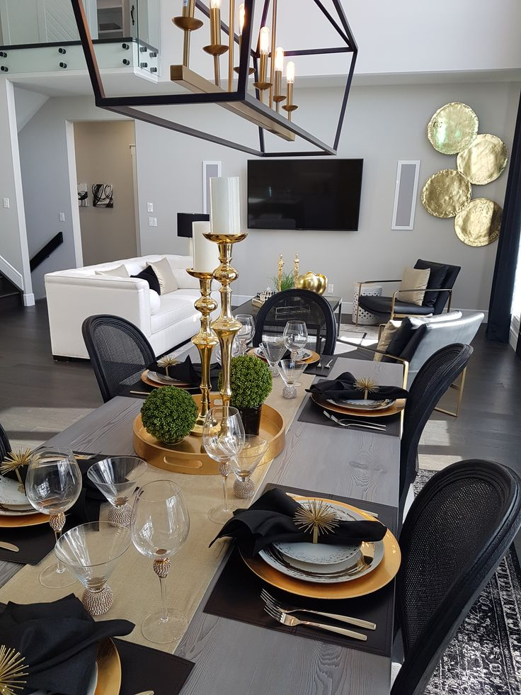 beautiful dining room with black and gold touches and unique lighting.