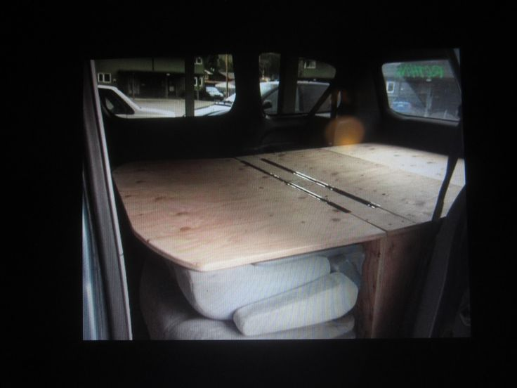 A box with a front flap that rests on the folded middle seats. A friend of his built this for $70. Copied from the middle of this post: http://thegroveguy.blogspot.com/2011/06/toyota-sienna-van-conversion.html?m=1