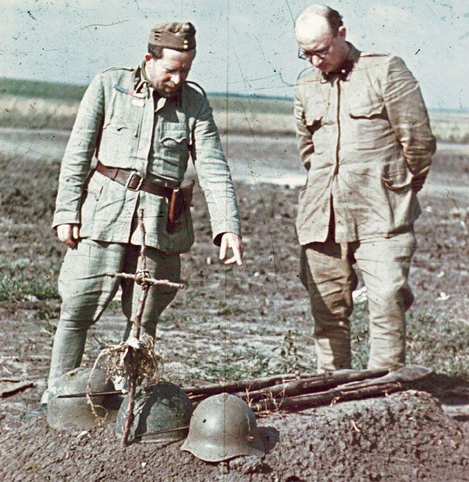 Magyar katonák elesett ellenséges katonák sírjait vizsgálják.
