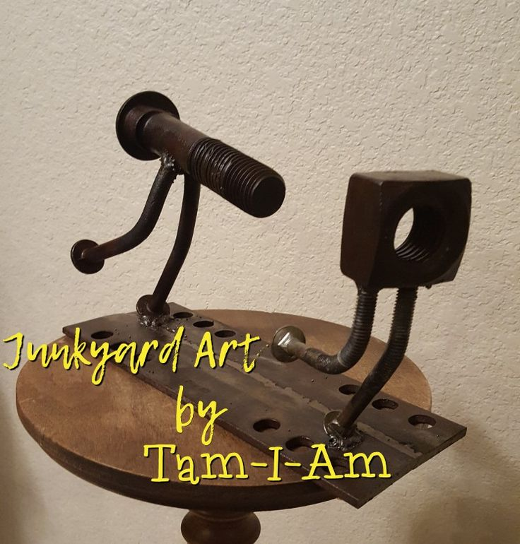 "Junkyard Art by Tam-I-Am. ""The Chase"" is comprised of a large nut and bolt and 4 smaller carriage bolts. Repurposed scrap metal art."