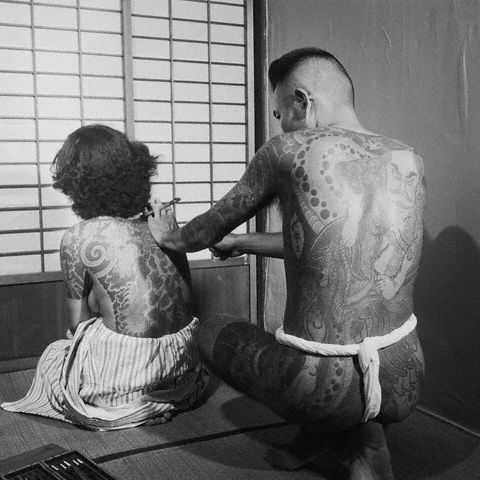A Japanese tattoo artist works on the back of a woman, Tokyo, Japan, 1946  by Horace Bristol