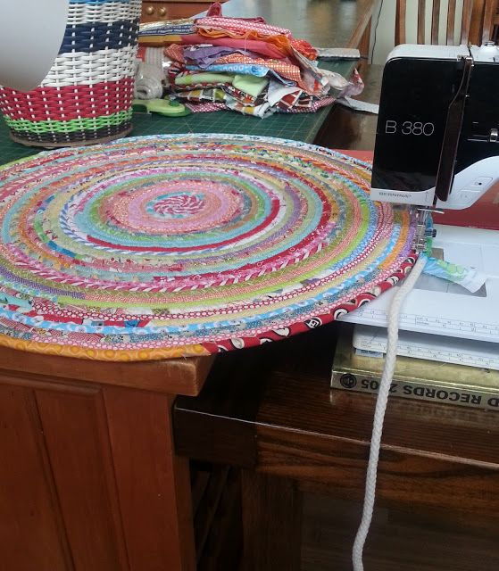 Machine-sewn rug made with strips of fabric wrapped around cotton cord and zig-zagged together.