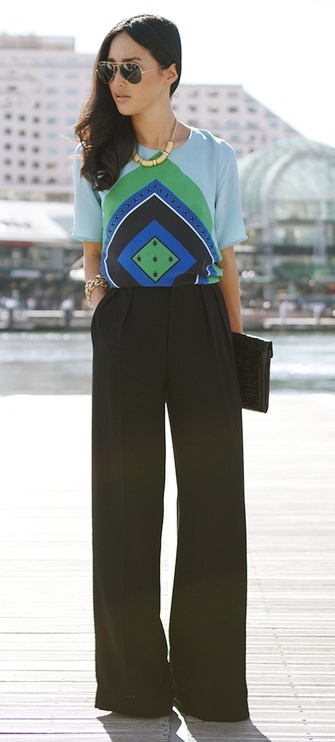 Black wide leg trousers, blue & green graphic print blouse, clutch, gold accessories
