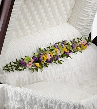 The FTD® Trail of Flowers™ Casket Adornment is a gorgeous accent piece that offers an extra touch of floral beauty at their memorial service. Green hydrangea, pink spray roses, yellow freesia, lavende