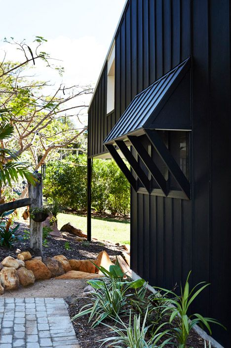 The black timber structure, added to one side of the original house (by Vokes and Peters), features overhanging eaves and large windows that open onto its wooded setting on the Sunshine Coast.