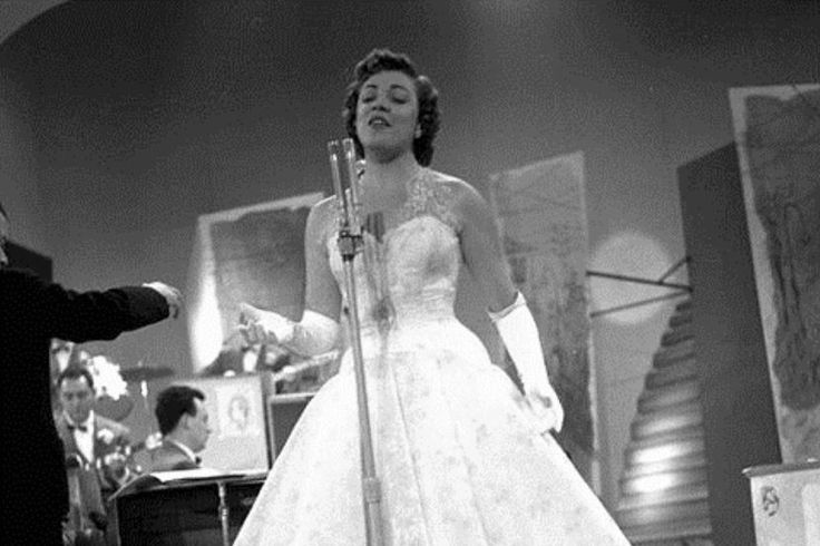 "Carla Boni at the Sanremo Festival in 1953. She won the competition with the song ""Viale d'autunno"" [Autumn Boulevard]. In the picture, on the left: conductor Cinico Angelini."