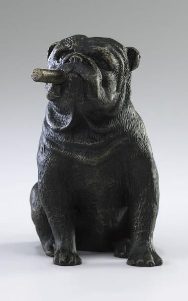 "This humorous sculpture features a gruff looking bulldog smoking a cigar. Made of iron with an Old World finish. Measurements: 5.5"" height x 3.5"" width x 4.5"" d"