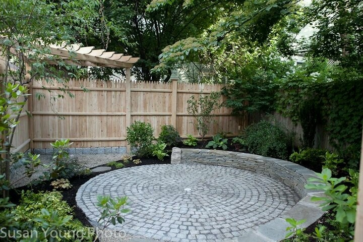 Reclaimed granite cobble circular patio with stacked bluestone seating wall and custom cedar pergola. Cambridge, MA. Design & installation by A Yard & A Half Landscaping Cooperative.
