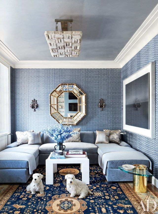 The family dogs find a cozy spot to relax in the beautifully blue living area of this Michael S. Smith–designed duplex penthouse in Chicago | archdigest.com