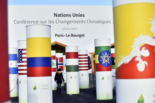 A woman walks past pillars with the Nations' national flags attending the COP 21 UN climate conference, decorating the exterior of the venue hall, on November 26, 2015, in Le Bourget, north of Paris, ahead of the 21st Session of the Conference of the Parties to the United Nations Framework Convention on Climate Change. - AFP