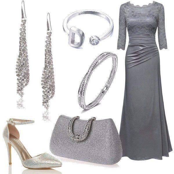 Elegantissimo e raffinato il vestito lungo color grigio perla, con corpetto ricamato, da indossare con delle décolleté con cinturino alla caviglia color argento e una borsa con paillettes. Luminosi son i gioielli che completano la proposta: un paio di orecchini con pendenti, un bracciale e un anello con la lettera iniziale.