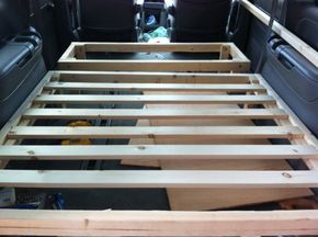 Guy used slats and thin plywood instead of 3/4 ply. Also two sections -- so small one acts as table while large one folds to act as bench seat. Pretty cute. Nothing holds the thing down to keep it from sliding back and forth (no front-rear). Also does not form fit outlines of van along the edges. Minivan Camper Conversion