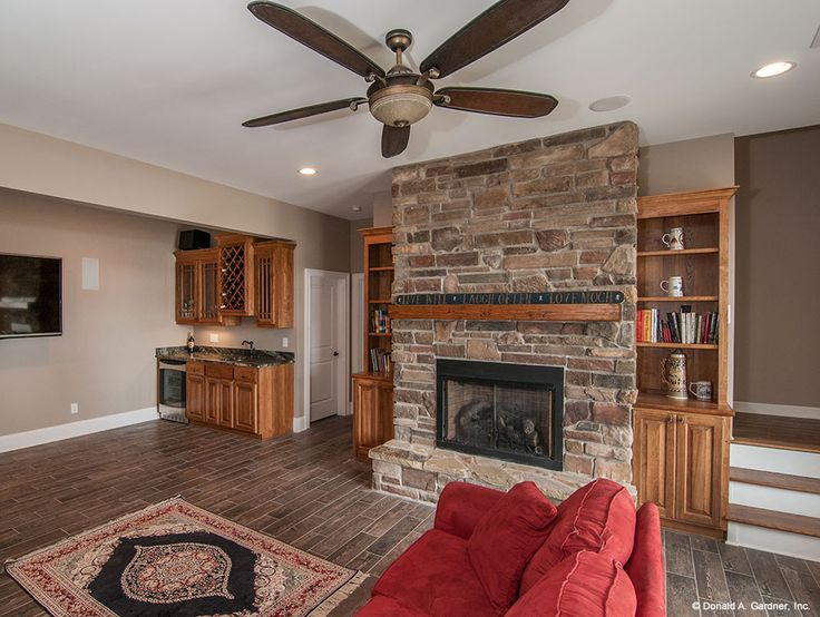 Walkout basement rec room with stone fireplace built ins for Donald gardner house plans with walkout basement