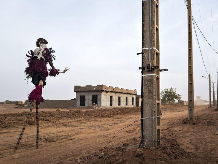 Strassenszene aus Mali mit einem vogelartig verkleideten Menschen, der auf Stelzen geht.